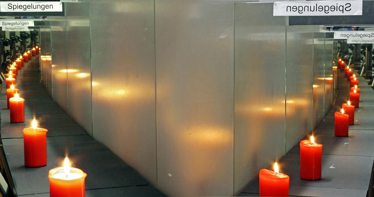 Spiegelungen einer brennenden Kerze