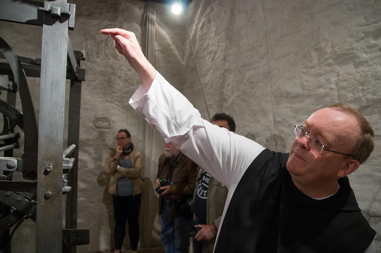 Pater Prior Johannes Brügger erläutert die Funktionsweise der Turmuhr
